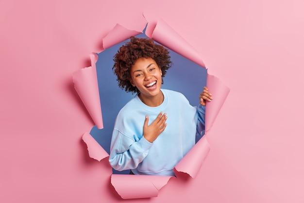 Счастливая темнокожая молодая женщина выражает искренние эмоции, держит руку на груди, широко улыбается, показывает белые зубы