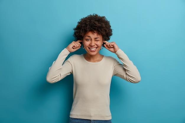 Felice giovane donna dalla pelle scura ignora la musica ad alto volume e tappi le orecchie con le dita