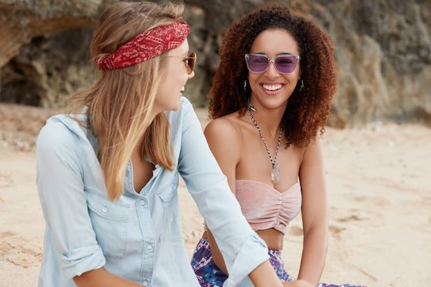 幸せな暗い肌の若い女性は彼女のガールフレンドを見て喜びながら笑い、同性の関係を持って、海の近くのビーチで一体感を楽しみます。