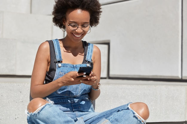 Happy dark skinned youngster with curly haircut, reads pleasant text message, watches funny video, types feedback, sits in lotus pose at stairs outside, wears denim ragged dungarees, surfes online