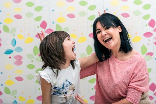 幸せな娘と母の指で角を作る