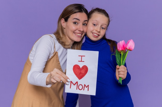 Happy daughter giving greeting card and tulips flowers for her surprised and smiling mother celebrating mother's day standing over purple wall