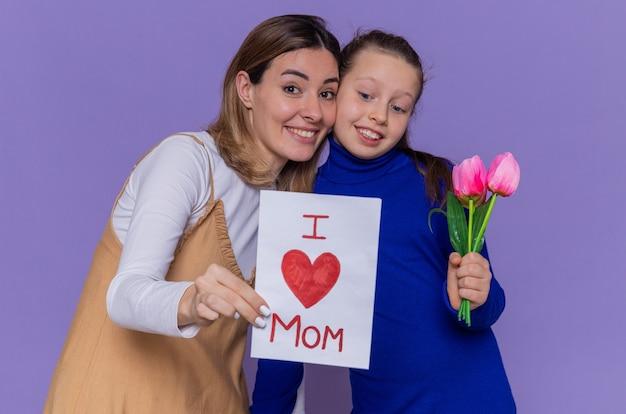 Figlia felice che dà biglietto di auguri e fiori di tulipani per sua madre sorpresa e sorridente che celebra la festa della mamma in piedi sopra il muro viola