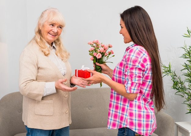Happy daughter giving wrapped gift box and flower bouquet to her mother