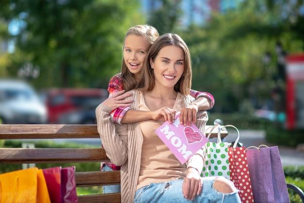 Счастливая дочь обнимает свою маму, сидя на скамейке в парке