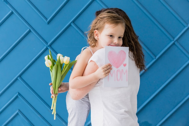Happy daughter hugging her mother with holding flowers and greeting card against blue backdrop