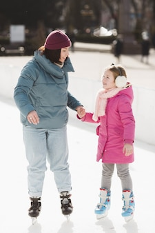 Happy daughter and mother ice skating