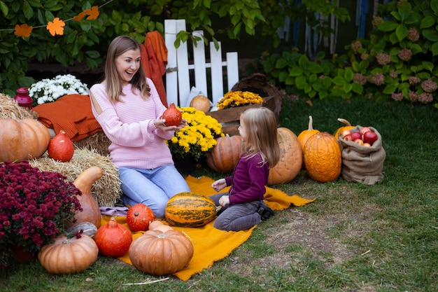 Happy daughter and mother with pumpkin outdoors
