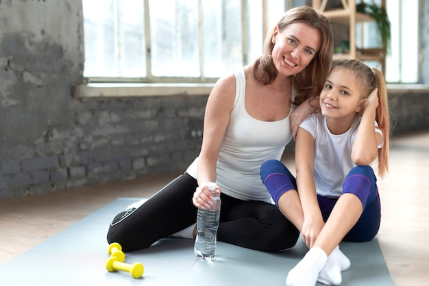 Happy daughter and mother on yoga mat posing