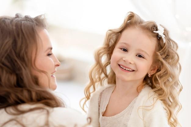母と遊ぶ幸せな娘。笑顔でカメラを見ているかわいい女の赤ちゃん。