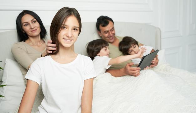 행복한 딸. 아침에 가족과 시간을 보내는 동안 카메라를 보며 웃고 있는 예쁜 10대 라틴 소녀의 초상화. 부모, 어린이 개념