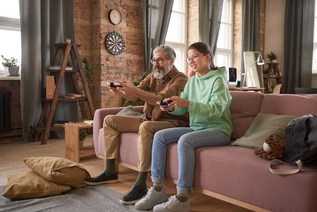 幸せな娘は彼女の父と一緒にソファに座って、家で余暇の間にビデオゲームをプレイします