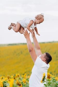 ひまわり畑でパパと幸せな娘。ひまわり畑で楽しんで幸せな家族。お父さんはひまわり畑に娘を投げます。家族concept.selectiveフォーカス