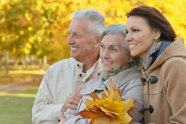 秋の公園で休んでいる先輩の両親と幸せな娘