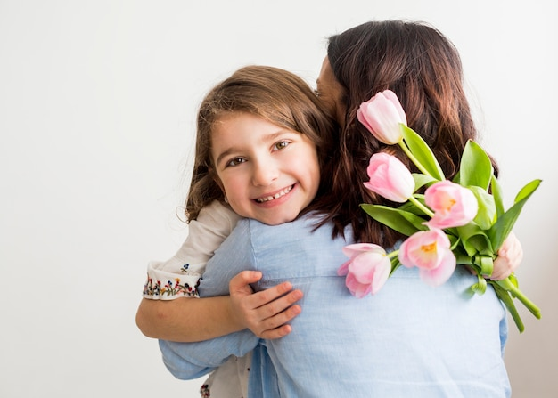 Happy daughter with tulips hugging mother