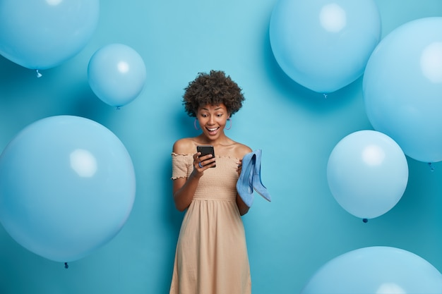 Happy day and celebration concept. positive dark skinned woman chats in social networks, wears long beige dress and holds blue shoes, chooses best outfit to look brilliant, isolated on blue wall