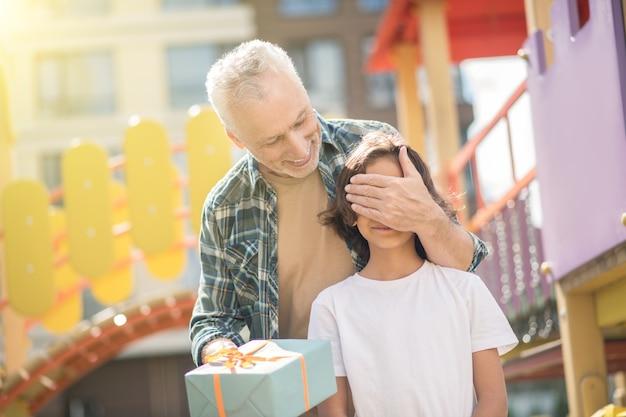 Счастливый день. счастливый отец делает подарок своему сыну, и оба выглядят взволнованными