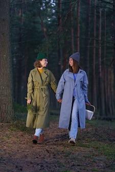 친구 2명의 여자 친구와 함께 자연 속에서 행복한 하루는 황혼에 베리나 버섯을 따는 가을 숲을 걷는다