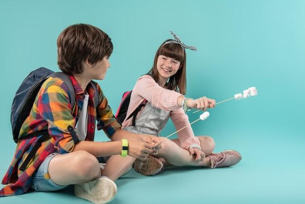 幸せな日。棒を持ってそれぞれの隣に座っているインスピレーションを得た素敵な学童