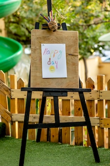 Happy day wooden easel in garden, kid zone with warm colours and painting accessories