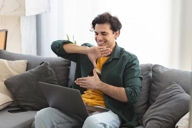 Счастливый глухой молодой кавказец использует язык жестов во время видеозвонка с помощью ноутбука, сидя на диване у себя дома
