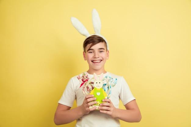 ハッピー。飾る。黄色のスタジオの背景にイースターバニーとして白人の少年。ハッピーイースターのご挨拶。美しい男性モデル。人間の感情、顔の表情、休日の概念。コピースペース。