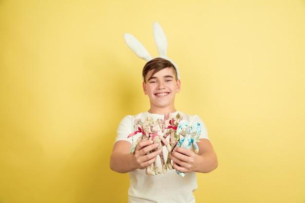 Счастливый. украшение. кавказский мальчик как пасхальный кролик на желтом фоне студии. поздравления с пасхой. красивая мужская модель. понятие человеческих эмоций, выражения лица, праздников. copyspace.