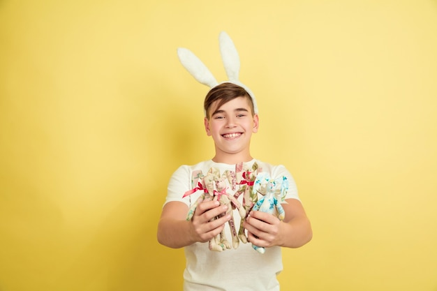 Happy. decorating. caucasian boy as an easter bunny on yellow studio background. happy easter greetings. beautiful male model. concept of human emotions, facial expression, holidays. copyspace.