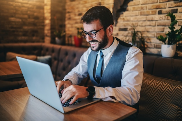 Happy dedicated handsome bearded caucasian businessman in suit and with eyeglasses sitting in cafe and using laptop for work.