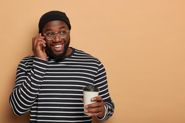 어두운 피부를 가진 행복한 delghted 남자는 쾌활한 전화 대화를합니다.