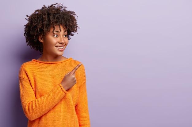 幸せな喜びのアフロアメリカ人女性は友人の新製品を示し、このオブジェクトを購入するように説得します