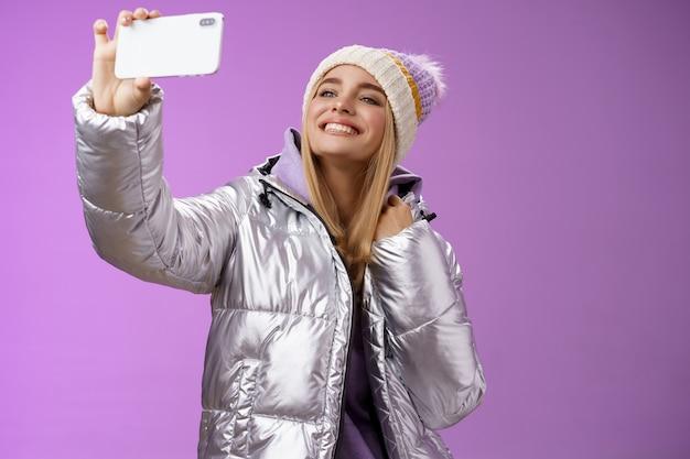 행복 한 기쁘게 평온한 공정한 머리 매력적인 유럽 여자 실버 겨울 재킷 모자를 들고 스마트 폰 수평으로 셀카 미소 휴대 전화 디스플레이, 보라색 배경을 복용.