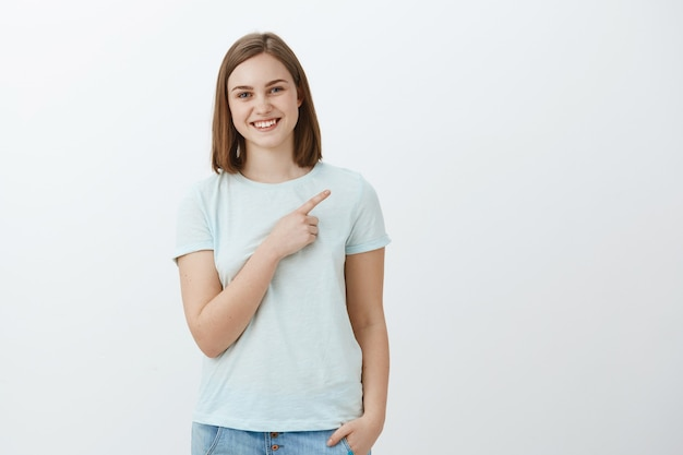 Happy delighted and carefree young woman pointing at copyspace