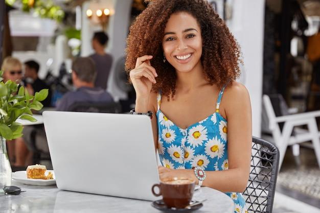 Счастливая довольная женщина-фрилансер с кудрявыми волосами и темной кожей, носит блузку с синим цветочным принтом, работает на портативном компьютере