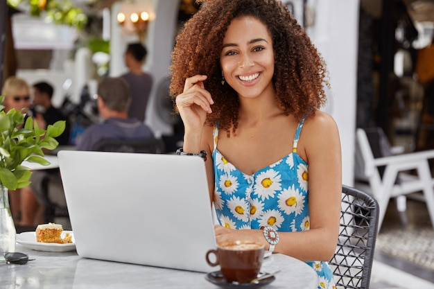 Happy delighted female freelancer with curly hair and dark skin, wears blue flower printed blouse, works on portable laptop computer