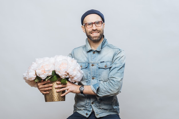 Happy delighted male buys bouquet of flowers for special occasion, wears denim jacket and denim shirt