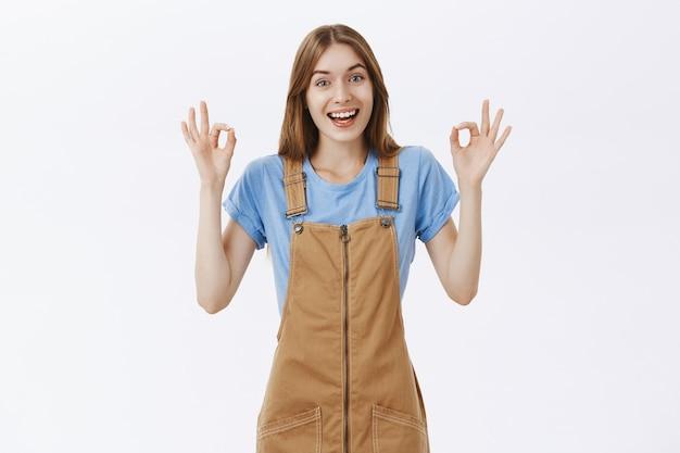 Счастливый, довольный симпатичная девушка показывает нормальный жест в знак одобрения, нравится и соглашается