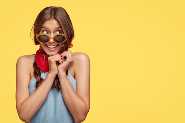 Happy delighted pretty girl with curious expression, keeps hands under chin, wears trendy sunglasses, anticipates for miracle, stands against yellow wall with free space for your text.