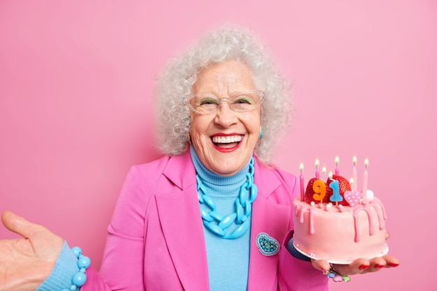 Happy delighted senior woman smiles from joy feels beautiful and energized celebrates her 91st birthday wears fashionable festive clothes holds tasty cake with candles