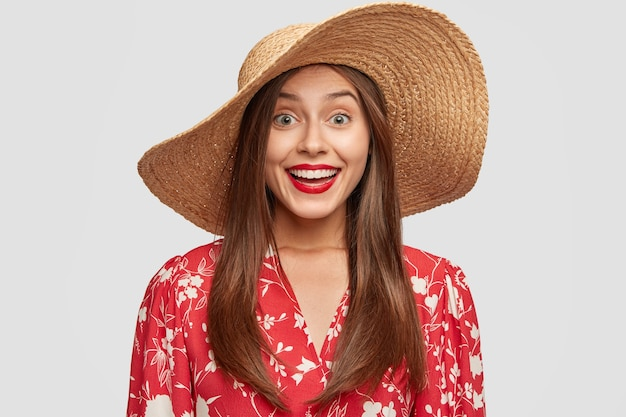 Happy delighted tourist has broad smile while speaks with stranger, wears stylish straw hat, red blouse
