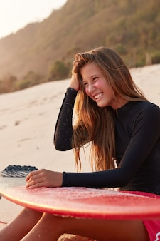 Happy delighted woman sits at reef break, dressed in swimsuit, giggles positively, holds surfboard