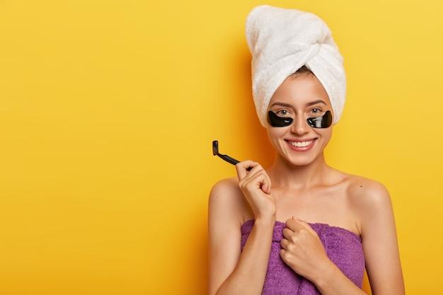 순수한 피부를 가진 행복하고 기쁜 여자, 그녀의 몸을 아끼고, 면도날을 들고, 목욕과 면도를 준비하고, 긍정적으로 미소 짓습니다.