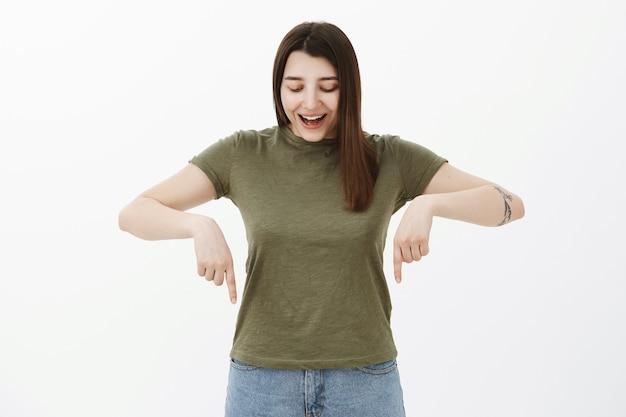 Felice felice giovane bruna europea di 20 anni con il tatuaggio in t-shirt sorridente divertito e curioso con i denti bianchi come guardando e indicando un prodotto impressionante impressionante sopra il muro grigio