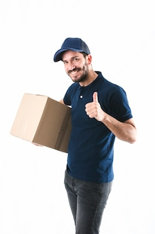 Happy delivery man holding cardboard box showing thumb up on white background
