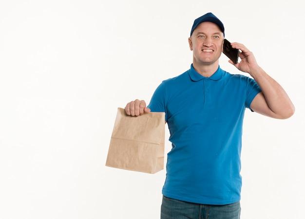 Счастливый доставщик держит бумажный пакет и смартфон
