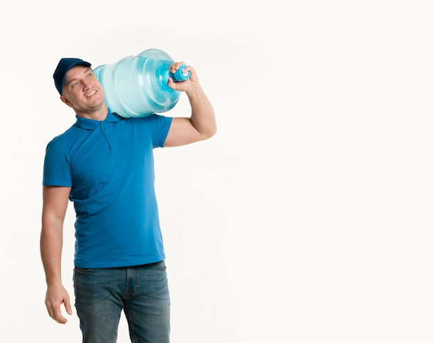 Happy delivery man holding water bottle on shoulder with copy space