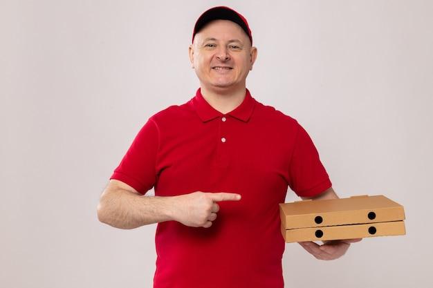 빨간 제복을 입은 행복한 배달원과 흰색 배경 위에 즐겁게 서서 웃고 있는 집게 손가락으로 가리키는 피자 상자를 들고 있는 모자