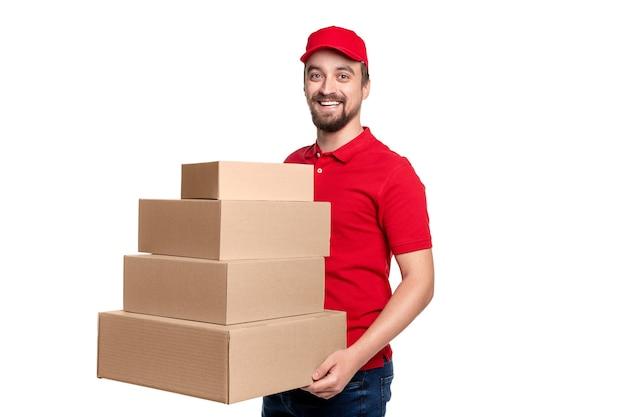 さまざまなサイズのカートンボックスのスタックを運び、白い背景に対してカメラを見て赤い制服を着た幸せな配達人
