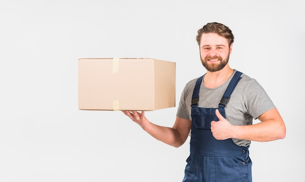 Happy delivery man with box showing thumb up