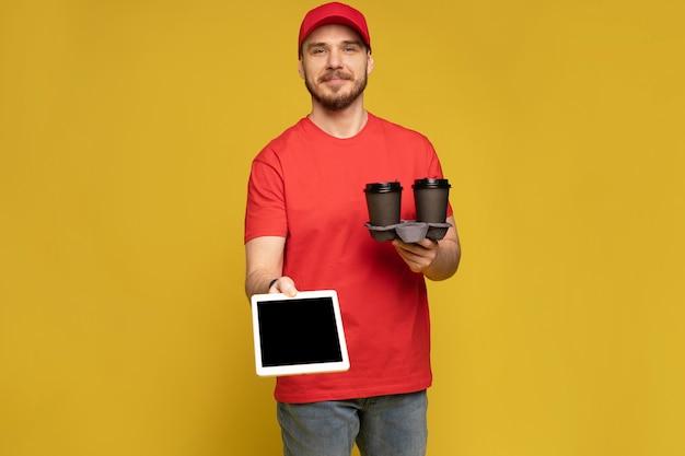 スタジオ分離黄色の壁にタブレットと幸せな配達人